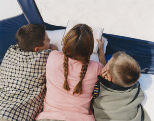 Mother reading to her two boys in camping tent
