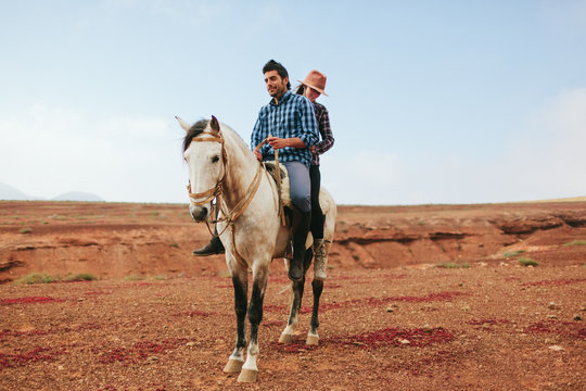 Young Couple riding a White Horse in the Desert