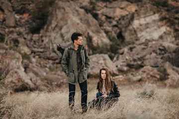 Fashionable young couple hiking in desert mountains