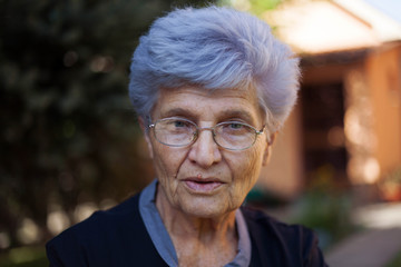 Portrait of a older woman with grey hair in a backyard