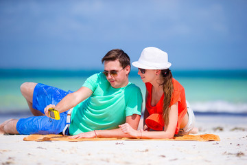Happy couple taking a photo on a beach on holidays