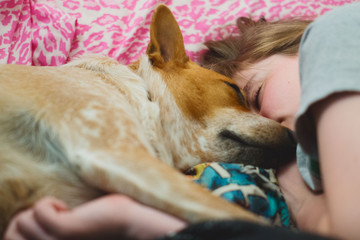 Teenager and her  dog sleep together face to face