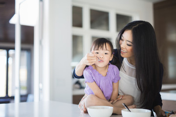 Mother and daughter eating breakfast in the kitchen together