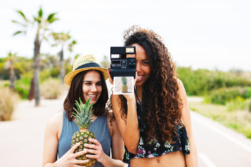 Female friends taking a photo of pineapple with a .