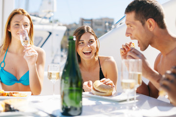 Group of friends having lunch on a luxurious yacht.