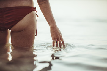 Buttocks of a Woman Standing in the Sea