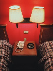 An end table in a cheap hotel room with cigarette butts in an ash tray, an old phone, and two lamps