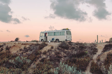 Bus sitting on top of sand dunes during sunrise