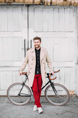 Man standing in a front of a bicycle.