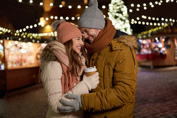 happy young couple with coffee at christmas market