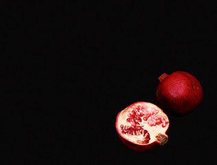 Flat lay. Top view. Pop art. Minimalist art. two half pomegranate fruit lay on black table