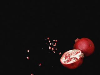 Flat lay. Top view. Pop art. Minimalist art. two half pomegranate fruit lay on black table