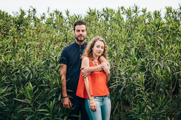 Young couple in front of a wall of laurels