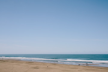 Flat blue ocean with big beach in California