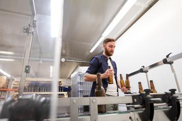 Fototapeta men with bottles on conveyor at craft beer brewery