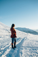 stylish young woman in red coat looks forward at the snowy trail ahead