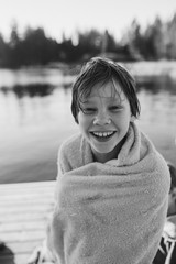 Young happy boy warming up with towel after jumping lake