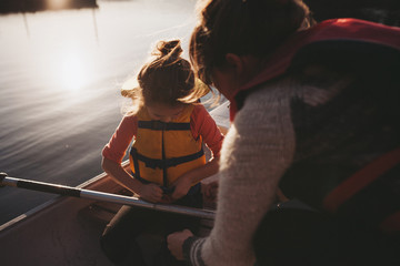 Young mom helping little girl with lifejacket