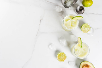 Alcoholic cocktail recipes and ideas. Avocado and lime margarita with salt, on a white marble kitchen table. Copy space top view