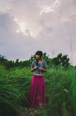 Asian woman standing in the green grass field in the cloudy day