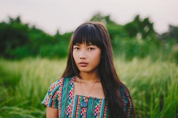 Asian woman portrait in the green grass field