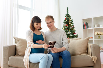 happy couple with ultrasound images at christmas