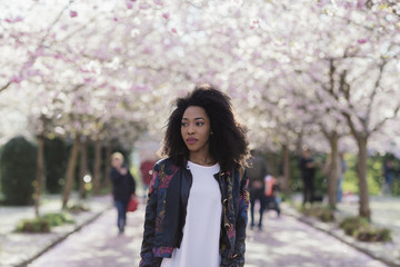 Young stylish black woman standing under cherry blossom trees