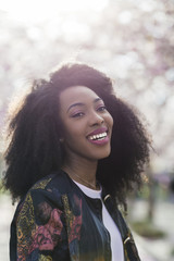 Portrait of young stylish black woman smiling in a park