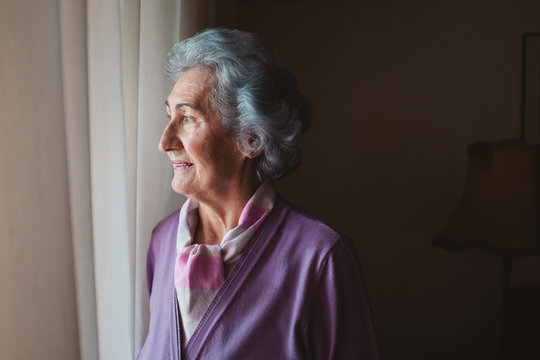 Beautiful Senior Woman Looking Though the Window