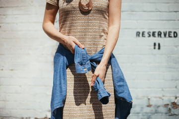 Girl tying denim shirt around her waist with brick wall background