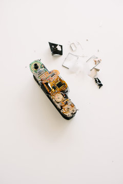 A broken film camera sitting on a white table with parts scattered.