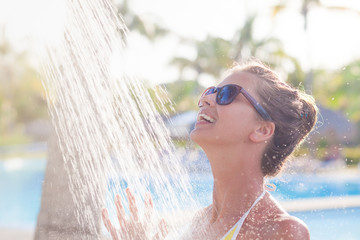 young woman refreshing in shower near pool