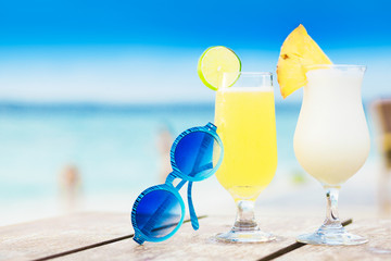 two delicious fruit cocktail and sunglasses by the beach