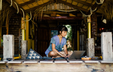 Casual young woman working on laptop in tropical house