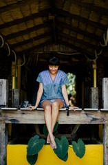 Asian woman sitting on the wooden balcony in tropical house