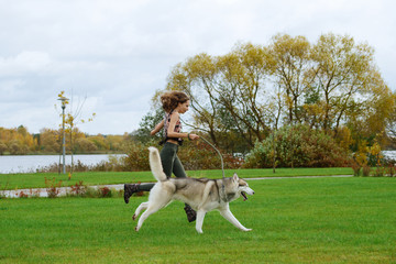 Girl playing with husky dog in city park. Jogging with dog.
