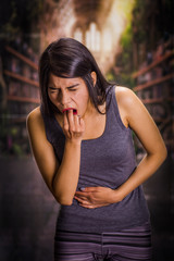 Beautiful and lonely girl suffering of anorexy, holding her stomach and putting his fingers in her mouth to induce to vomit, a blurred background