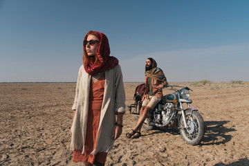 Young Couple Traveling Through Desert on Motorbike