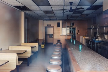 An abandoned, empty diner restaurant with booths and stools and a counter