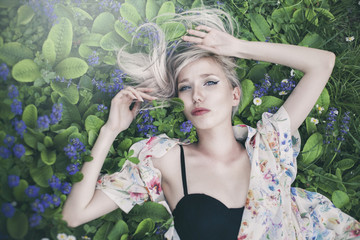 Young beautiful woman with blond hair, freckles and blue eyes lying in the grass