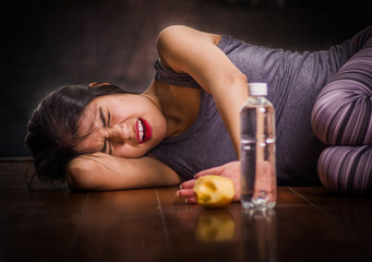 Beautiful girl suffering from anorexy, screaming and laying on the wooden floor with her arms around her head suffering pain with an apple and a bottle of water in front, in a blurred background