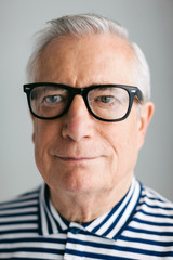 Portrait of an elderly man with rimmed glasses.