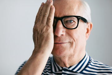 Portrait of an elderly man covering his eye with a hand and smiling.