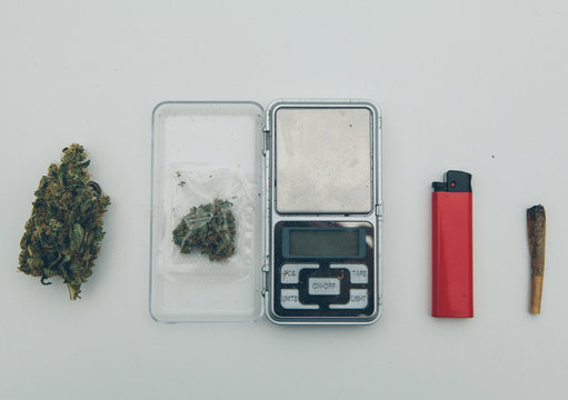 Marijuana bud with small bag, scales, lighter and joint.
