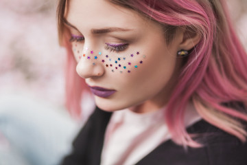 Young girl wearing colorful stars on her face