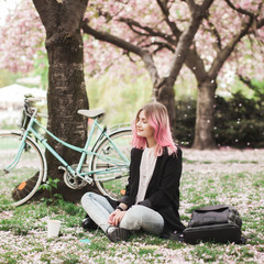 Girl with pink hair sitting on the grass in the blossoming park