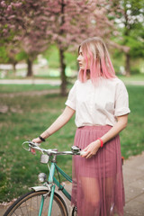 Girl with a pink hair on the bike in the blossoming park