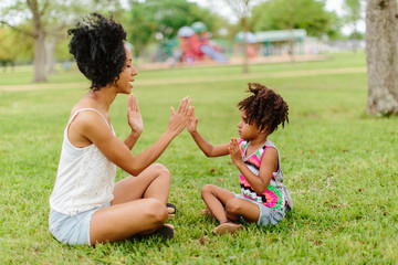 A mother and daughter playing patty cake in the park