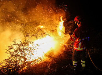 A firefighters works to extinguish flames from a forest fire in Cabanoes near Lousa
