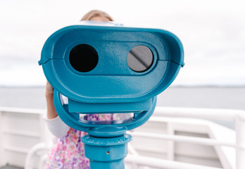 girl using a viewfinder telescope on a ferry trip